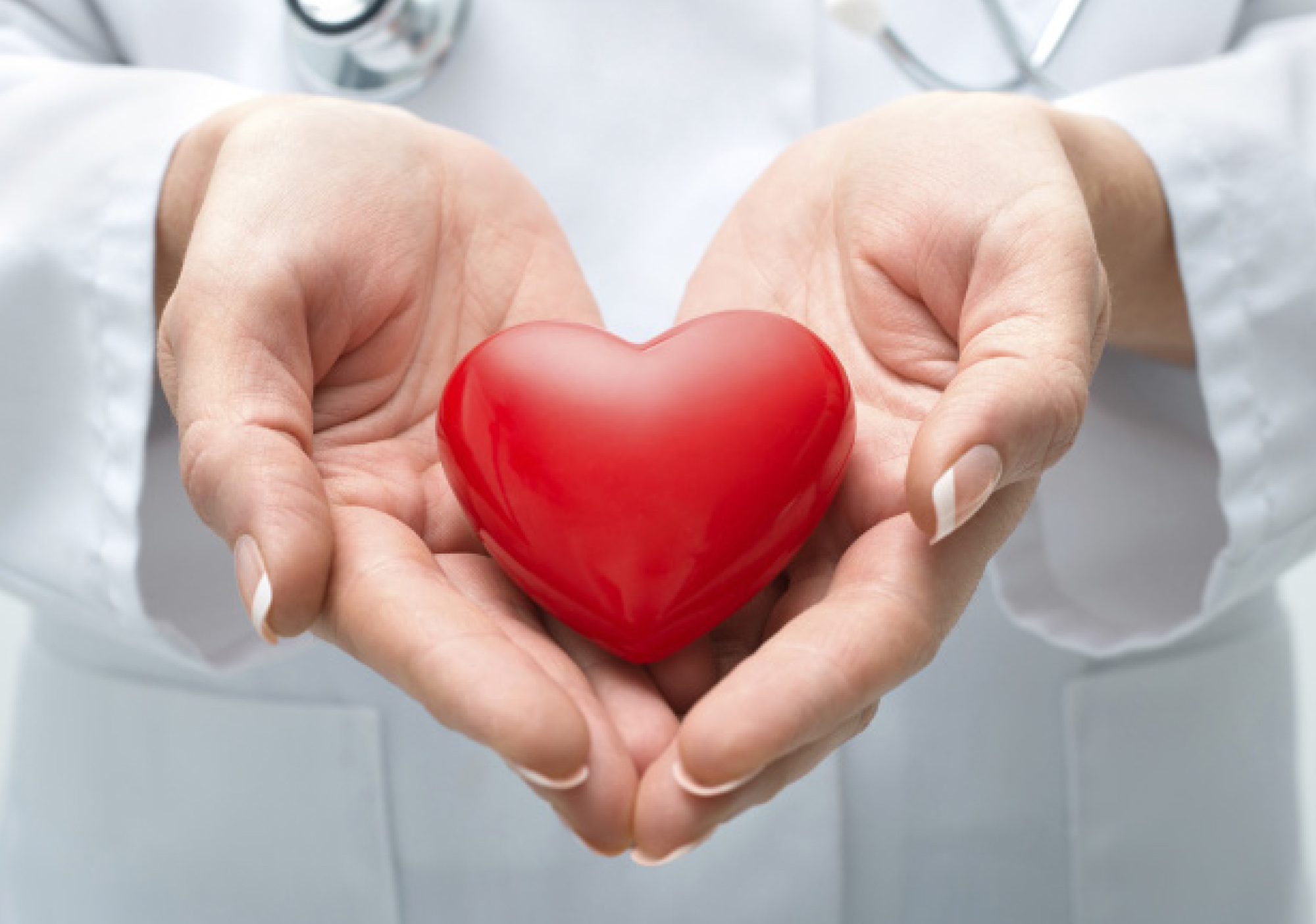 Doctor at tri-cities cancer center holding a heart-shaped object to say thank you to the community